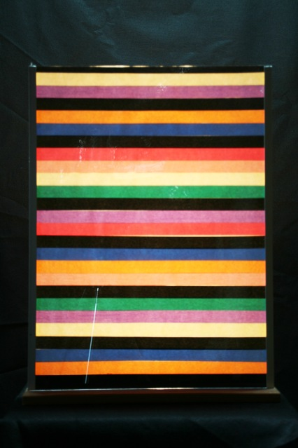 "Al Wong, ""Color Bars"" ©2012, 24""H x 18""W, Plastic, paper, colored tape, and aluminum. (View 2 - lit from behind)"